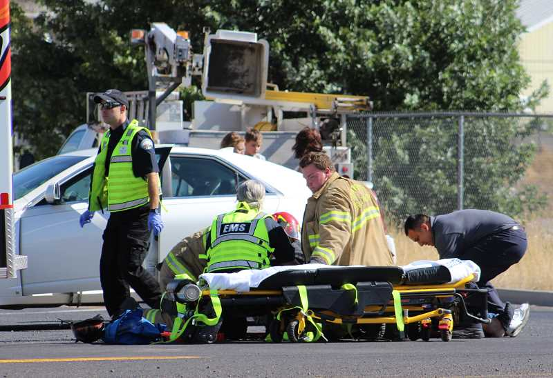 HOLLY M. GILL/MADRAS PIONEER - A Madras man was injured Monday in a collision between his motorcycle and a Ford Explorer. Personnel from Jefferson County Emergency Medical Services and Jefferson County Fire District prepare the motorcyclist for transport to the hospital.