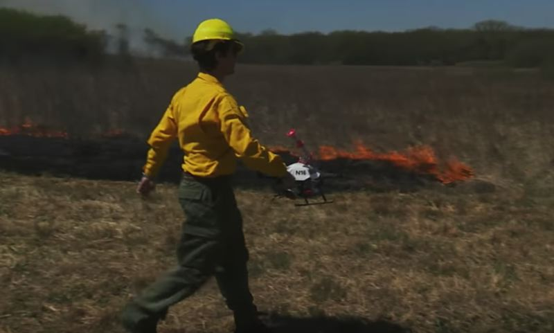 STILL SHOT COURTESY OF UNIVERSITY OF NEBRASKA - A firefighter in Nebraska gets ready to place a drone in a field to deposit firestarting devices near an existing blaze. Drones are being increasingly used among fire agencies to manage fires with reduced risk to human life.