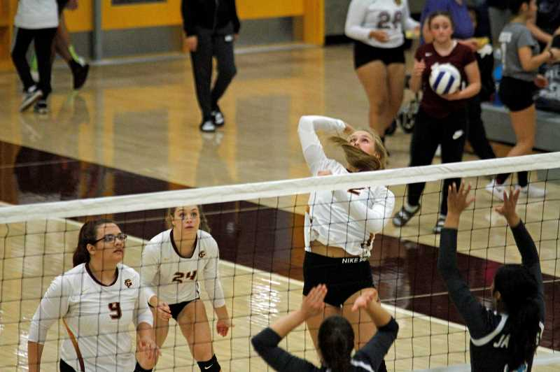 STAFF PHOTO: WADE EVANSON - Forest Grove's Amanda Rebsom (22) goes up for a spike while teammates Elena Sanchez (9) and Alexis Goodman (24) watch in anticipation.