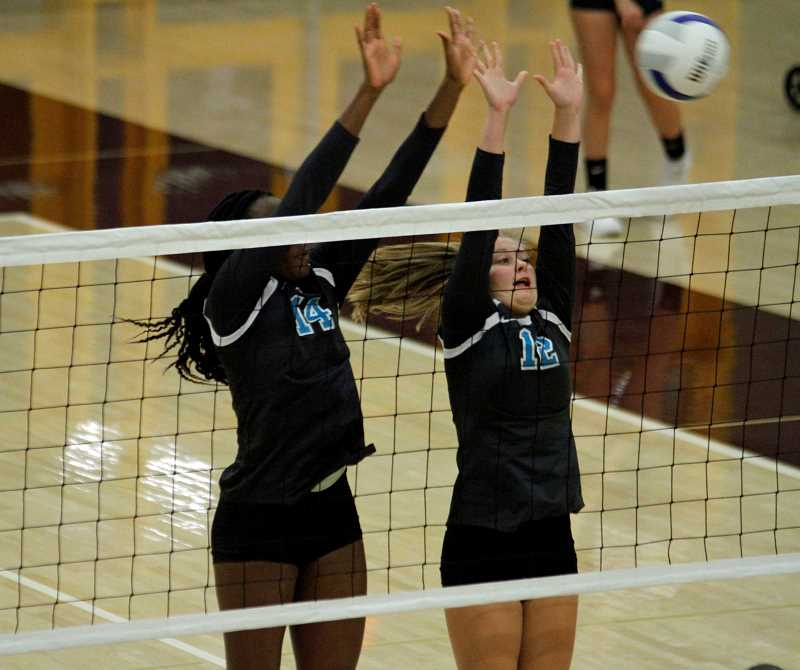 STAFF PHOTO: WADE EVANSON - Century sophomore Barakat Rahmon (14) and senior Hannah Brown (12) go up to block a kill attempt during the Jaguars' game against Forest Grove, Sept. 12, at Forest Grove High School.