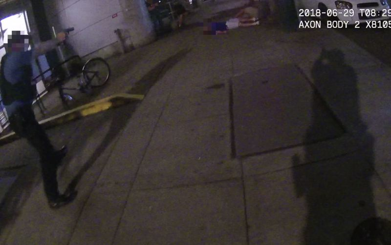 SCREENSHOT: PORTLAND STATE UNIVERSITY FOOTAGE - Footage from Officer James Dewey's body camera shows Officer Shawn McKenzie on the left and his own shadow on the right in the moment Jason Washington was shot multiple times. Washington, in a gray shirt, is on the ground at the top of the photo, next to a man in a blue shirt.