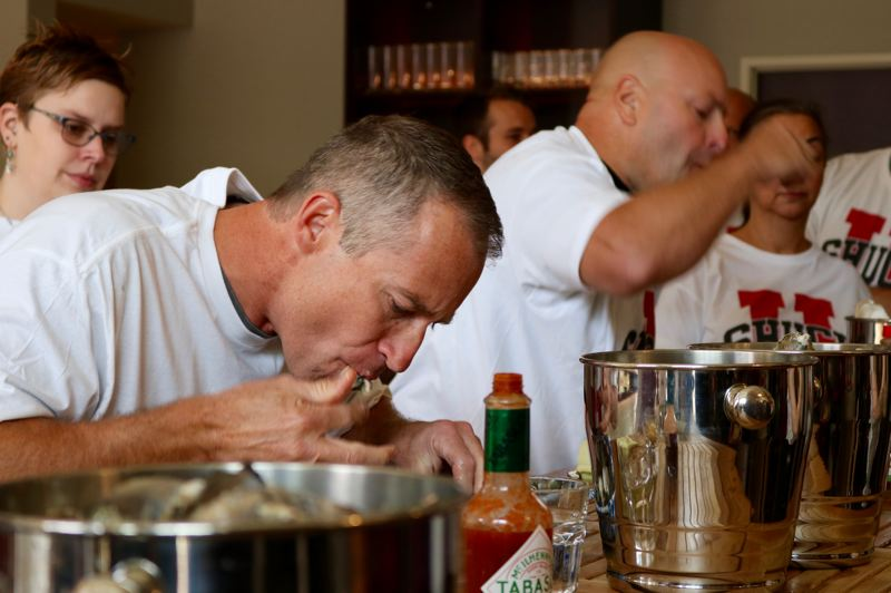 TIMES PHOTO: ZANE SPARLING - Nathan Burk of the Lake Oswego Police Department (foreground) and other first responders munched on hundreds of raw oysters during a speed-eating competition for charity on Saturday, Sept. 15.