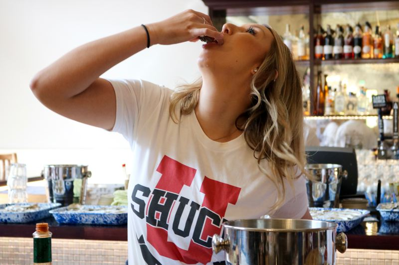 TIMES PHOTO: ZANE SPARLING - LOPD Officer Johnna Richards slurps down a raw oyster on Saturday, Sept. 15, at Ways & Means Oyster House in Bridgeport Village.