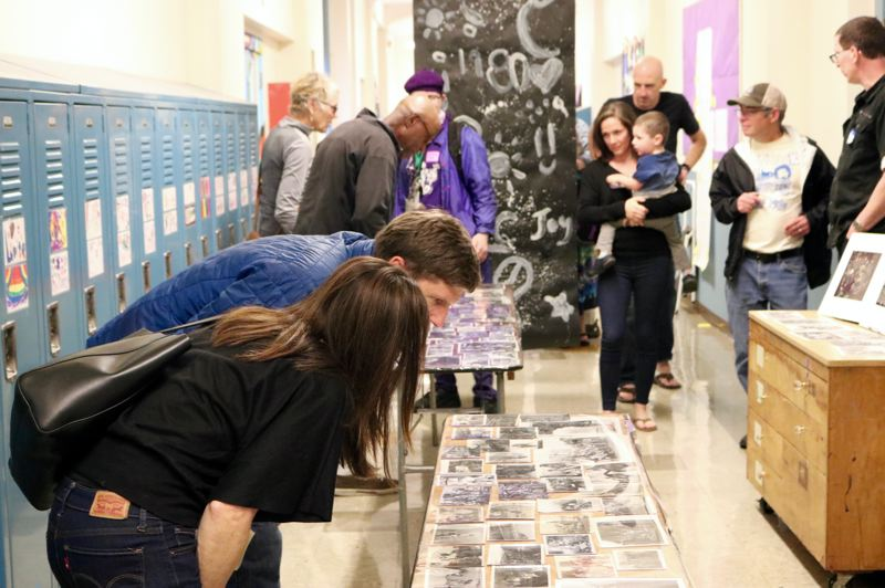 TRIBUNE PHOTO: ZANE SPARLING - Former MLC students examine old photos during the 50th anniversary celebration of the downtown Portland Public School on Saturday, Sept. 15.