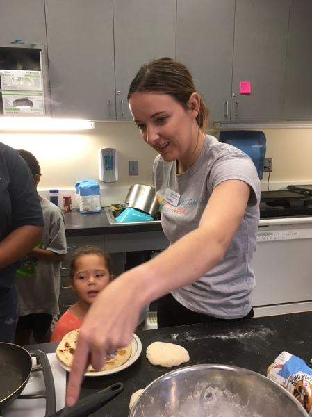 TIMES PHOTO: PETER WONG - Megan Cohen, Beaverton community services coordinator, helps 3-year-old Jaedin Gilyard complete cooking of her unleavened flatbread known as chapati during the Beaverton International Celebration on Saturday, Sept. 15.