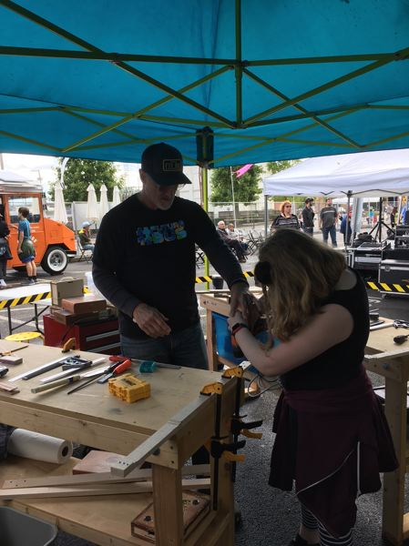 TIMES PHOTO: PETER WONG - Vince Radostitz, a teacher on the technological innovation team of the Beaverton School District, assists Molly Carter, a fifth-grade student at Vose Elementary School in making a cigar-box guitar at the Portland Mini Maker Fair last weekend.