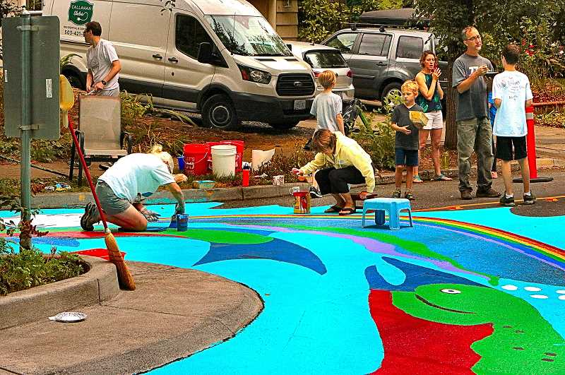 DAVID F. ASHTON - Many Eastmoreland neighbors took turn painting, while other took a break to talk with each other, during the annual repainting of this section of S.E. Bybee Boulevard.