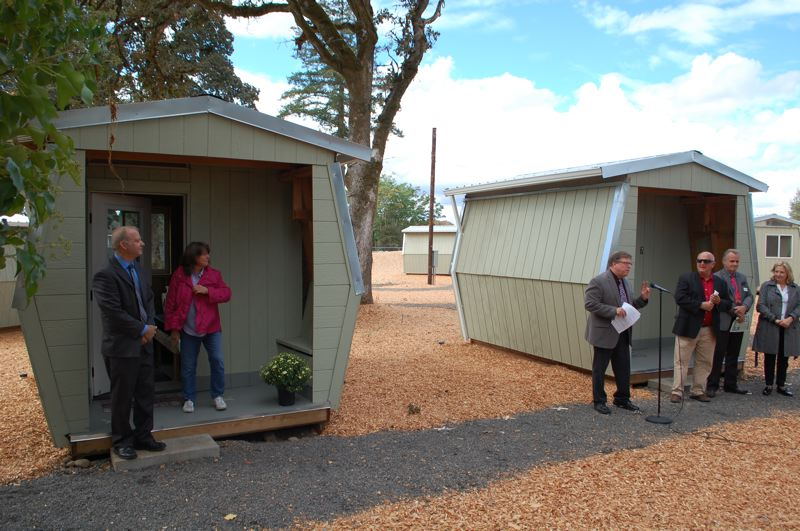 PHOTO BY: RAYMOND RENDLEMAN - Clackamas County Commissioners Paul Savas and Martha Schrader symbolically open one of the sleeping pods during the Sept. 13 ceremony for the countys newly constructed Vets Village.