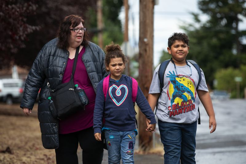 JONATHAN HOUSE - Tara Mixon walks home with her daughter Starla, center, and son Jack after school.
