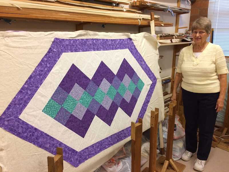 HERALD PHOTO:CAROL ROSEN - One of the many quilts. Both the quilts and the teaching to make them are quite famous throughout the region. Some of the sessions have had more than 1,000 attendants. Congregant Pat Hershberger stands next to a design ready for quilting.