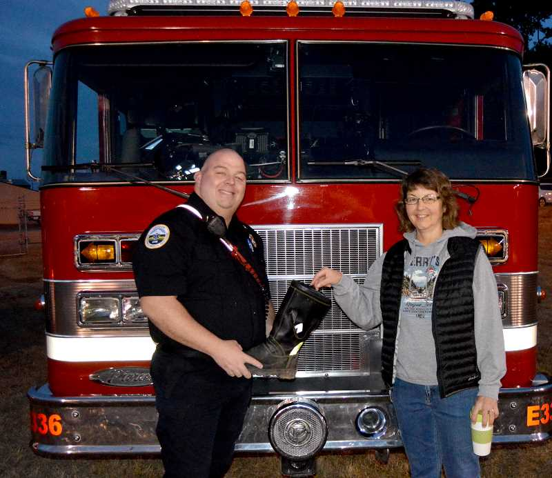 PIONEER PHOTO: CINDY FAMA - Kelly Stephens puts a donation in the boot at last Fridays CHS football game. The money raised by the Colton Volunteer Firefighters' Association will go to purchase a new defibrillator.