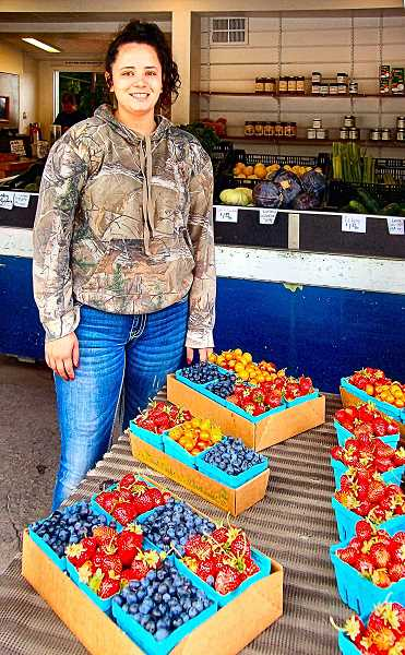 RITA A. LEONARD - Tori Ledesma shows some of the fresh berries on sale at Berry Good Farm Market on S.E. 28th, now under new ownership - just north of the Portland Rhododendron Garden.