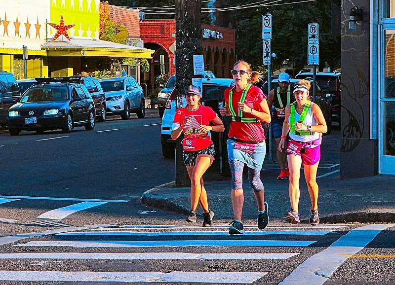 DAVID F. ASHTON - In Westmorelands business district, this trio of Hood-to-Coast runners crosses S.E. Bybee Boulevard at a brisk trot.