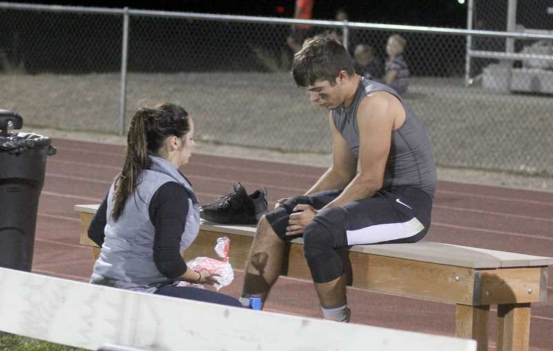 STEELE HAUGEN - Courtney Miller puts ice on injured Joe Russo during a Culver game.