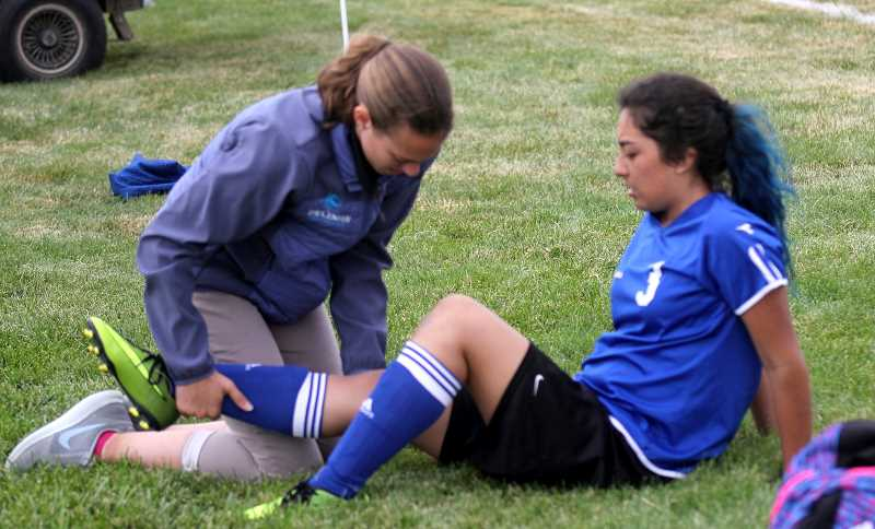 STEELE HAUGEN - New athetic trainer Nicole Porter helps soccer player Selma Sanchez with a possible knee injury. 