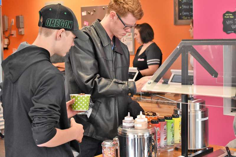 ESTACADA NEWS PHOTO: EMILY LINDSTRAND - Customers add toppings ot their desserts during the grand opening of Yo Treats Frozen Yogurt on Saturday, Sept. 15.