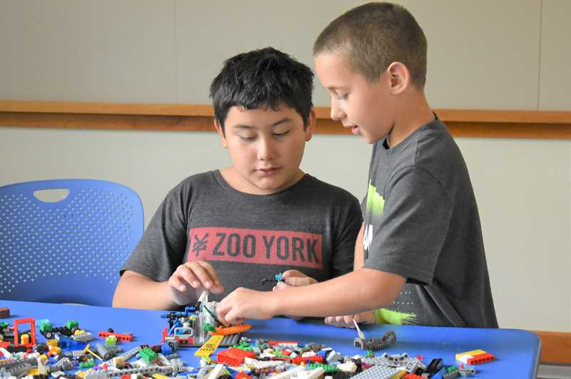 ESTACADA NEWS PHOTO: EMILY LINDSTRAND - Diego and Ben Seely build an animal sanctuary during a meeting of the Lego Creativity Club on Saturday, Sept. 15.