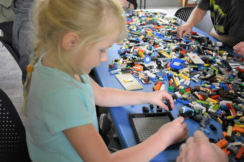 ESTACADA NEWS PHOTO: EMILY LINDSTRAND - A young participant in the Lego Creativity Club at the Estacada Public Library works on a new creation.