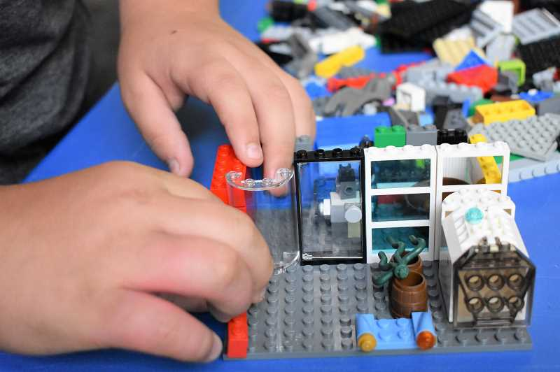 ESTACADA NEWS PHOTO: EMILY LINDSTRAND - Diego Seely works on an animal sanctuary built from Legos last weekend at the Estacada Public Library.
