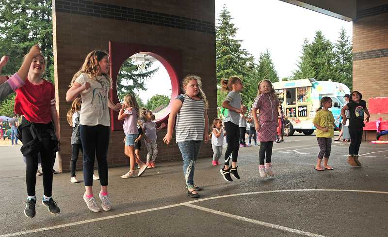 TIDINGS PHOTO: VERN UYETAKE  - Kids have fun showing off their moves to the dance music at the Trillium barbecue.