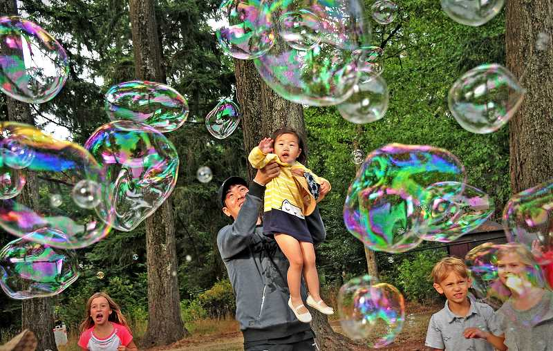 TIDINGS PHOTO: VERN UYETAKE  - Olivia Song and her dad Chris have fun trying catch giant soap bubbles.