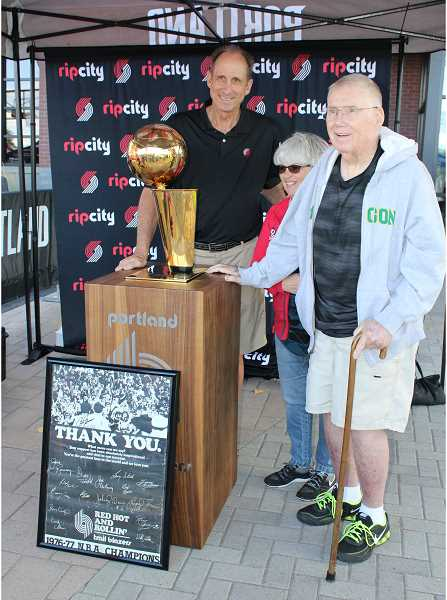 HOLLY M. GILL/MADRAS PIONEER - Former Blazer Bob Gross, a member of the 1977 championship team, poses with the team trophy and Sharon and Tom Miller, of Madras, longtime fans, who brought the poster in the foreground with them.
