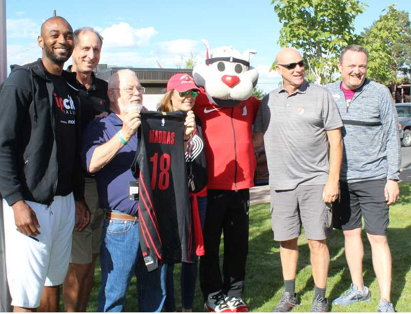 HOLLY M. GILL/MADRAS PIONEER - Madras Mayor Royce Embanks holds a Blazer jersey, surrounded by, left to right, Blazers television analyst Lamar Hurd, former player Bob Gross, sideline reporter Brooke Olzendam, play-by-play announcer Kevin Calabro, and Scott Loftin, a senior vice president at Moda.