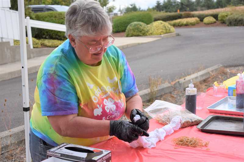 ESTACADA NEWS PHOTO: EMILY LINDSTRAND - Tami Guttridge prepares to tye dye t-shirts at the Springwater Community Fair on Saturday, Sept. 15.