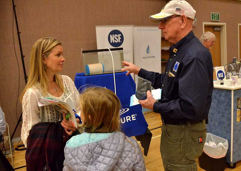 TIDINGS PHOTO: VERN UYETAKE - Julia, left, and Charity Hudnut learn about water filtration systems from John Bemis.