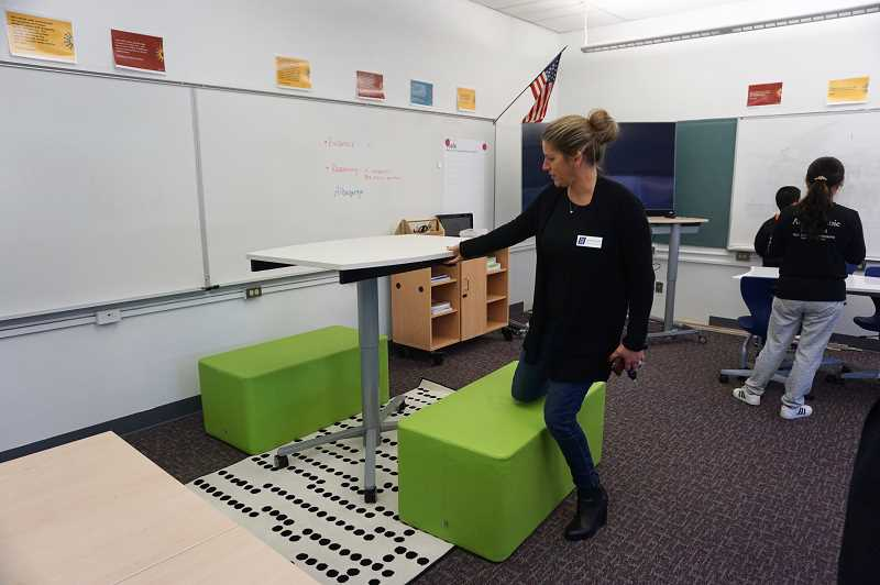REVIEW PHOTO: CLAIRE HOLLEY - Assistant Superintendent Jennifer Schiele demonstrates how desks in Lakeridge Junior High's model classroom can be raised or lowered for use standing or sitting.