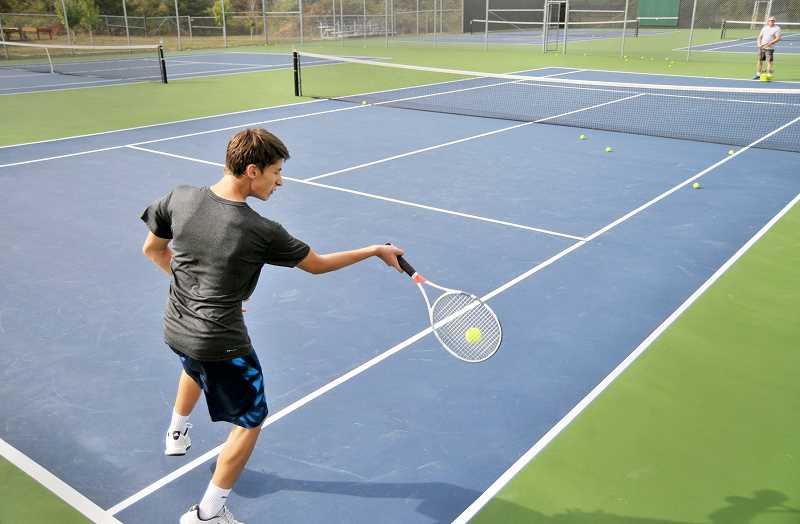 SETH GORDON - Spencer Lanier hits balls with head coach Dave Brown Friday on Newberg High School's freshly painted tennis courts.