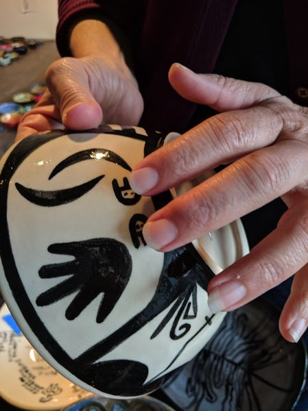 TRIBUNE PHOTO: JOSEPH GALLIVAN - Bowls included in Dana Lynn Louis project were painted by people who have experienced homelessness. This was signed with the double bear claw sign of a Hopi.