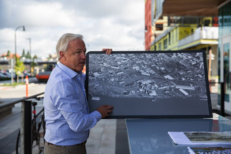 PAMPLIN MEDIA GROUP: ADAM WICKHAM  - Barry Cain shows off an image of the industrial site before his company bought and started developing it.