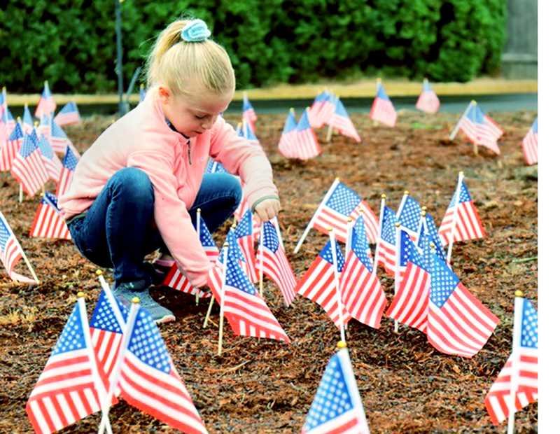 SETH GORDON - C.S. Lewis Academy student Audrey Jackson plants one of 300 small flags around the school's flagpole Sept. 11 as part of its Patriot Day event.