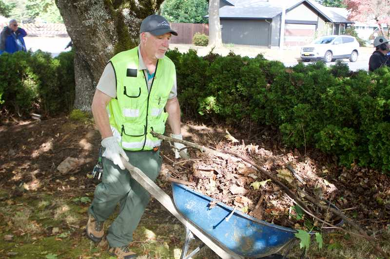 OUTLOOK PHOTO: CHRISTOPHER KEIZUR - During the launch of the new program, volunteers trimmed hedges, trees and removed debris from the yard of a disabled resident.