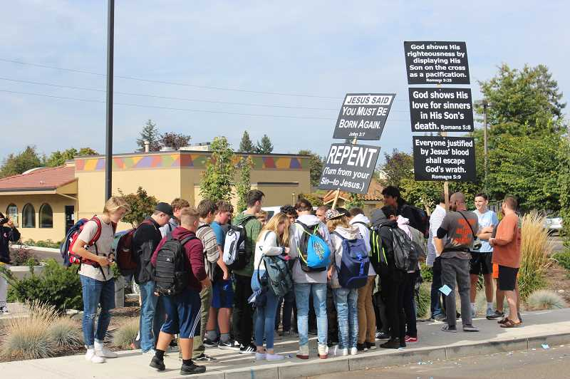 HERALD PHOTO: KRISTEN WOHLERS - 'Gospel Invasion Ministries' showed up at Canby High School on Friday, Sept. 21 with signs and megaphones.