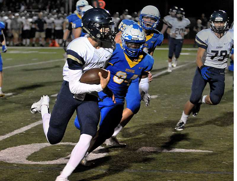 SETH GORDON - Canby quarterback Trent Wakefield eyes the endzone with Newberg linebacker Lawrence Lundgren in hot pursuit Friday night. The Tigers won 20-7.