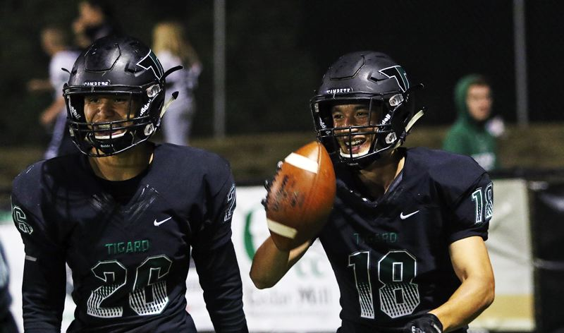 TIMES PHOTO: DAN BROOD - Tigard's Jazz Ross (left) and Josh Burns had plenty to celebrate on Friday during their team's 45-13 home win over Lincoln.