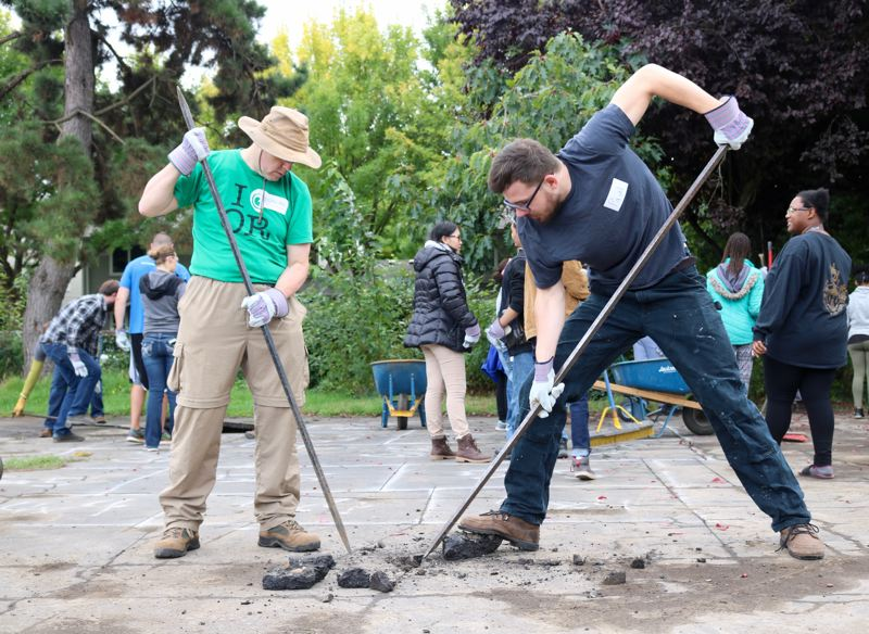 TRIBUNE PHOTO: ZANE SPARLING - Paul Lantow, right, volunteered for the depaving event on Saturday, Sept. 22 through his employer, AWS Elemental.