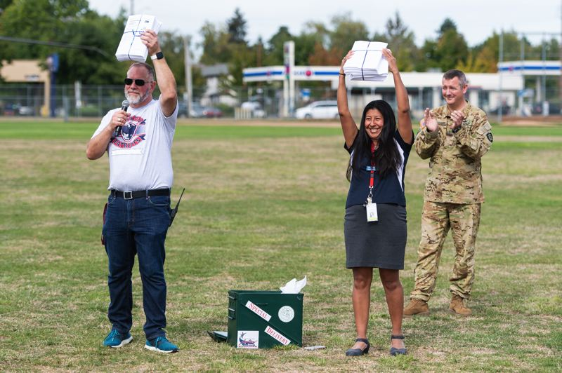 STAFF PHOTO: CHRISTOPHER OERTELL  - Poynter principal Jon Pede and assistant principal Sonta Thompson hold up tickets for each student and two of their family members, as well as every staff member, to attend the upcoming Oregon International Airshow.