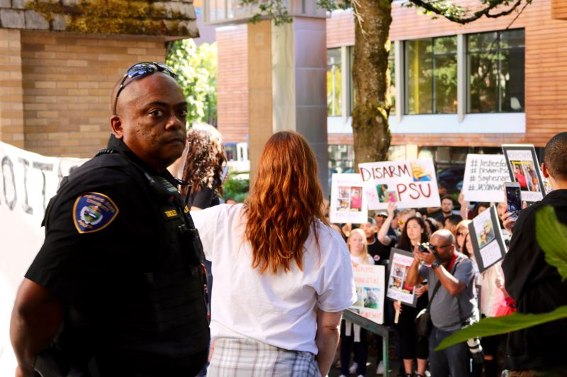TRIBUNE PHOTO: ZANE SPARLING - A Portland State University officer stands guard outside the Campus Public Safety building on Monday, Sept. 24. Protesters mourning the death of Jason Washington plan to 'occupy' the area outside the building.