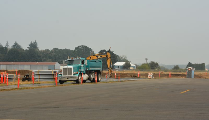 SPOTLIGHT FILE PHOTO - Construction equipment and trucks move dirt at the Scappoose Industrial Airpark for a project that will see a taxiway moved, to leave more space between aircraft. The airport is slated to get a small piece of the pie from a federal transportation grant package.