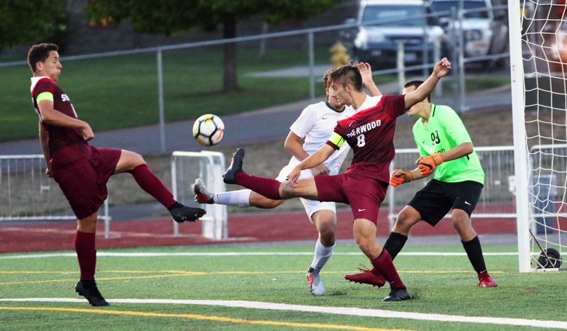 TIMES PHOTO: DAN BROOD - Sherwood senior Ty Vohland (left) and senior Caden Brandt (8) try to get their foot on the ball during the Bowmens 1-0 loss to West Linn.