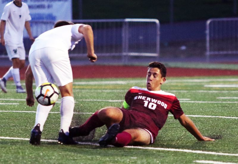 TIMES PHOTO: DAN BROOD - Sherwood senior Ty Vohland slides to knock the ball away from a West Linn player during the teams non-league match on Thursday.