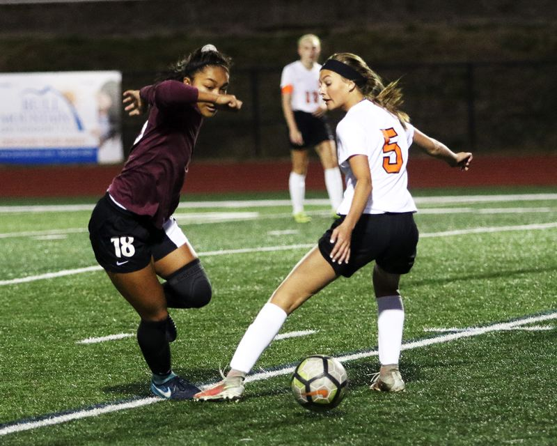 PAMPLIN MEDIA GROUP: DAN BROOD - Scappoose senior Lauren Whisenhunt (right) battles Tualatin sophomore Cally Togiai for the ball during Mondays match.