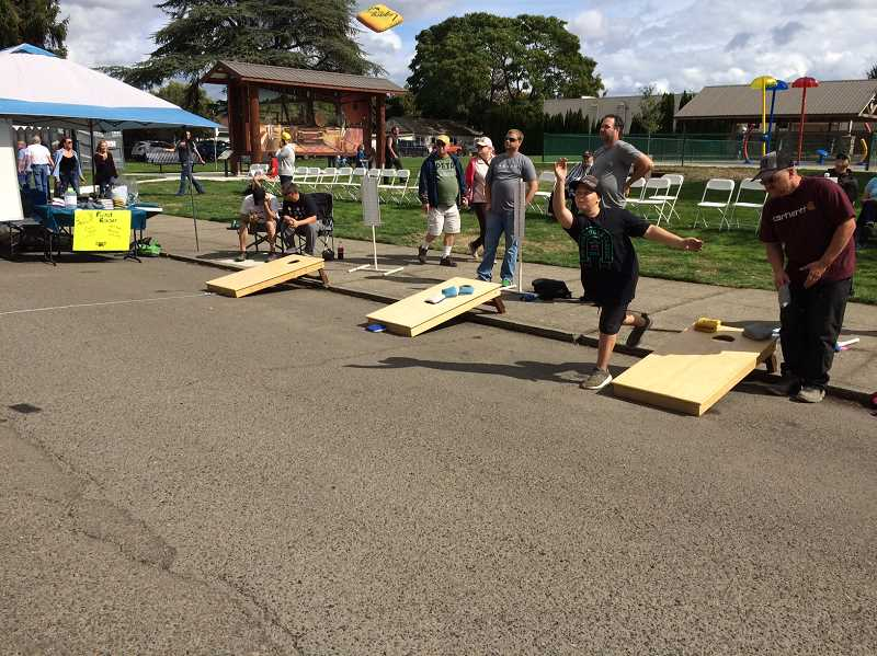 PIONEER PHOTO: CAROL ROSEN - Attendees enjoy playing corn hole during the festivities Saturday.