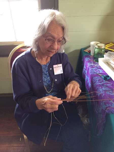 PIONEER PHOTO: CAROL ROSEN - Kathryn Henderson works with straw at the Apple Festival.