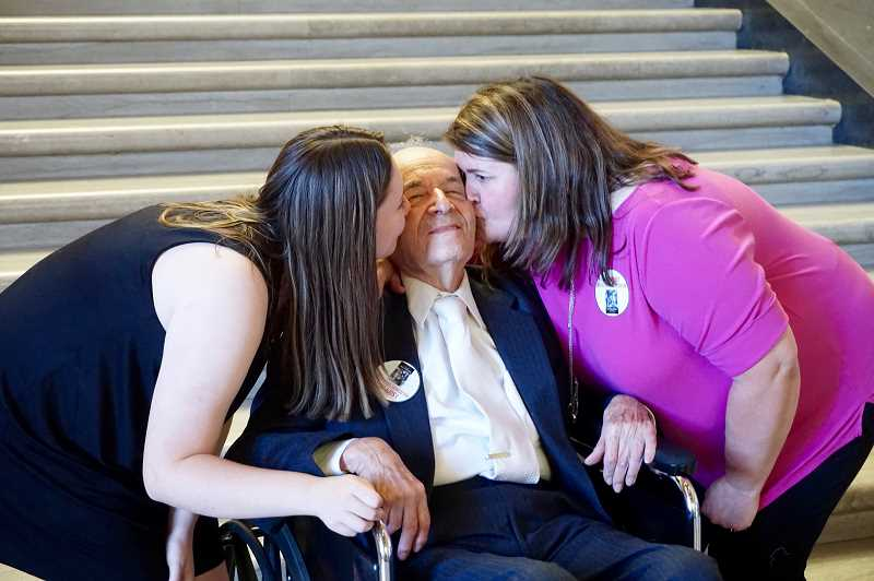 REVIEW PHOTO: CLAIRE HOLLEY - Claire Sarnowski (left) and her mother Carol give Holocaust survivor Alter Wiener double kisses on the cheek Tuesday in the rotunda of the state Capitol in Salem.