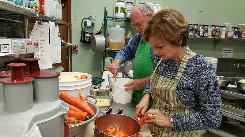 SUBMITTED PHOTO: MARIA BIGELOW - John Fowlks and Gayle Stickley prepare food for meals at the Lake Oswego Adult Community Center, where the city's Meals on Wheels program is based.