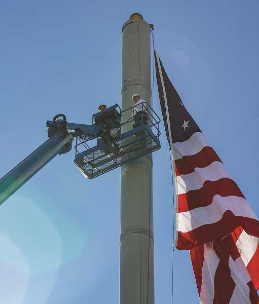 HOLLY SCHOLZ - Crook County Judge Seth Crawford, right, and Joe Sherman, a Rosendin Electric prefabrication manager, adjust the flag and rope at the top of the cell tower.